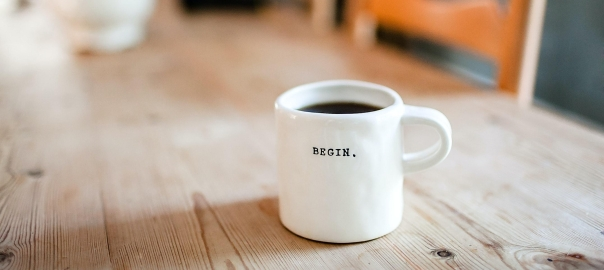 Coffee cup with BEGIN written on it set on a wooden table filled with coffee
