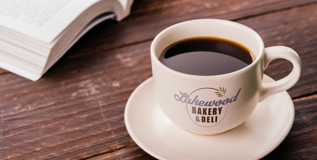 coffee cup with Lakewood Bakery & Deli logo on table